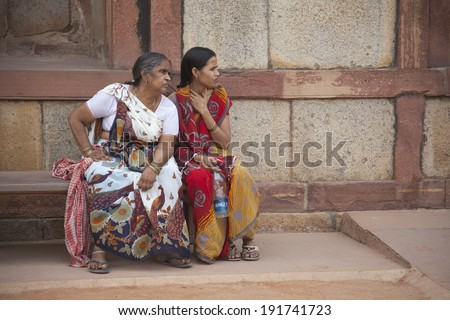 DELHI, INDIA, APRIL 21, 2013: Two women inside Jama Masjid mosque watching passers by. The mosque is located in the area known as Old Delhi. - stock photo