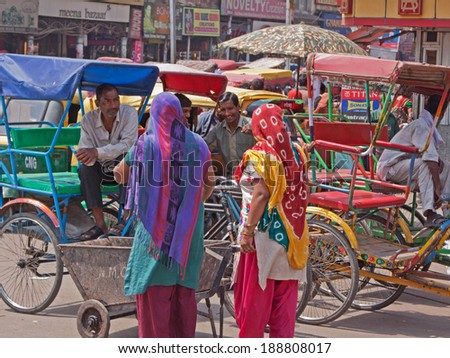DELHI, INDIA - MARCH 27, 2014: Owners of cycle rickshaws chatting to potential  customers in the Chandni Chowk area of old Delhi  - stock photo