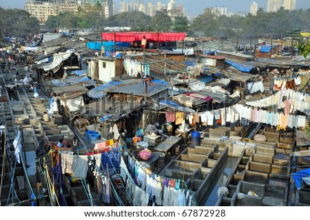 DELHI, INDIA - 5 NOVEMBER: Indian people work at Dhobi Ghat in Mumbai on November 5, 2009. Dhobi Ghat is the the world's largest outdoor laundry and work there nearly 200 dhobi families. - stock photo