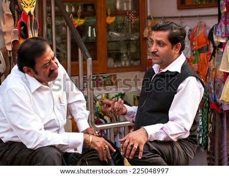 Delhi, India - November 6, 2011: two mannered men talking at premises of their shop. - stock photo