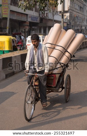 DELHI, INDIA - NOVEMBER 5: Unidentified  cycle rickshaw carries goods on November 5, 2014 in Delhi, India. Cycle rickshaw is popular mode of travel for short distance transits in the city. - stock photo