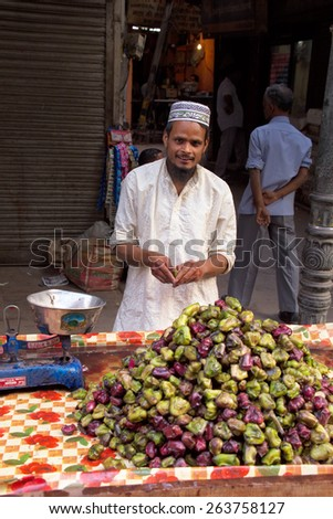 DELHI, INDIA - NOVEMBER 5: Unidentified man sells fruits from a stall on November 5, 2014 in Delhi, India. Street vendors are widly spread through out the city.  - stock photo