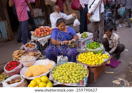 DELHI, INDIA-NOVEMBER 5: Unidentified woman sells fruits on November 5, 2014 in Delhi, India. Street vendors provide local people with fresh and cheap produce and are widly spread through out the city - stock photo