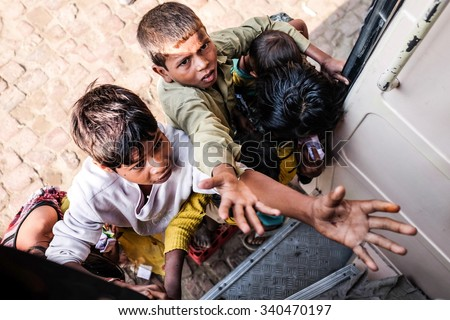 Delhi ,India . 25- October -2015. An unidentified beggar girl and boy begs for money from tourist . Poverty is a major issue in India. - stock photo