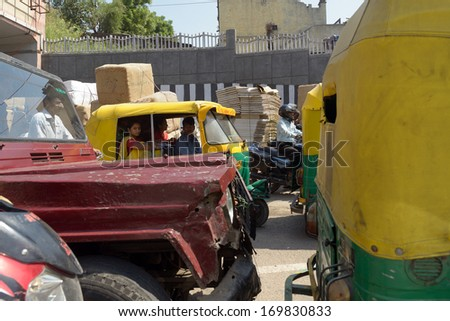 DELHI, INDIA - OCTOBER 01: Crowded street on October 01, 2012 in Delhi. Old, damaged car in foreground. - stock photo