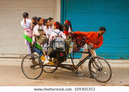 DELHI, INDIA - OCTOBER 27,: Unidentified girls ride a crammed private cycle rickshaw to school on October 27, 2009 in Delhi, India. Schools do not provide shared bus transportation in India. - stock photo