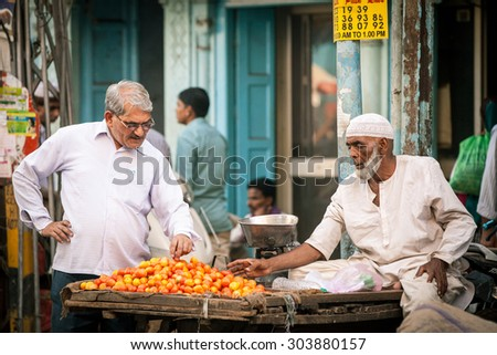Delhi, India - September 18, 2014: Indian man buying tomatoes from muslim vendor on the street of Old Delhi, India on September 18, 2014. - stock photo