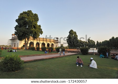 Delhi, India - September 18, 2013: Local people spend their leisure time in the afternoon, before the Diwan-i-Khas, the white building in Red Fort, Delhi, India.  - stock photo