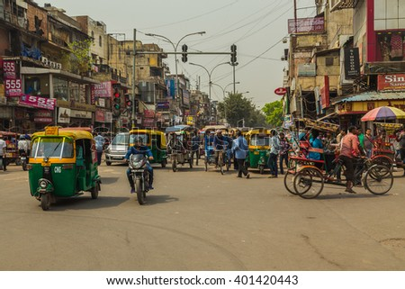 DELHI, INDIA - 19TH MARCH 2016: A view along streets of Delhi during the day showing buildings, Tuk Tuk Rickshaws, motorbikes and people. - stock photo