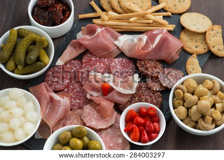 deli meat snacks, sausages and pickles on a blackboard, close-up, top view, horizontal - stock photo