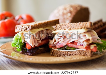 Deli style sandwich stacked with sliced roast turkey, fresh tomatoes, Jarlsberg cheese, green leafy lettuce, Spanish onions, sweet oat & wheat bread with a dijon ranch dressing.  - stock photo