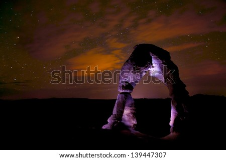 Delicate Arch at night against beautiful cloudy starry night sky - stock photo