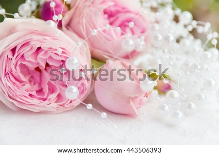 Delicate, beautiful roses soft pink color with white beads on a light background. A beautiful backdrop for weddings, cards, gift, place for text - stock photo
