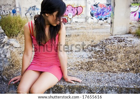 Delicate beauty sitting in a dirty place. - stock photo