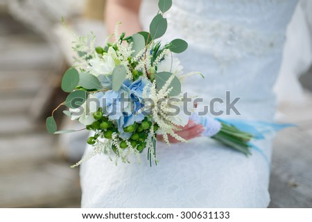delicate bouquet bride with blue ribbon Bride holding a beautiful composition with the blue and white flowers bright and original bridal bouquet - stock photo