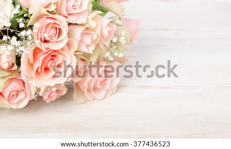 Delicate bouquet of fresh pink roses on a textured white wood background with copy space for your Valentines, Mothers Day, anniversary or birthday wishes - stock photo