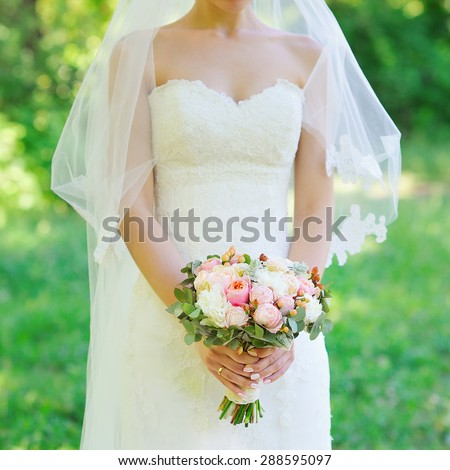 Delicate bride in wedding dress holding beautiful flower bouquet - stock photo