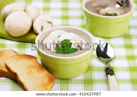Delicate cheese cream soup with mushrooms and crispy bread on a table - stock photo
