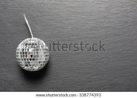 Delicate mirrored silver Christmas bauble on a dark slate surface - stock photo