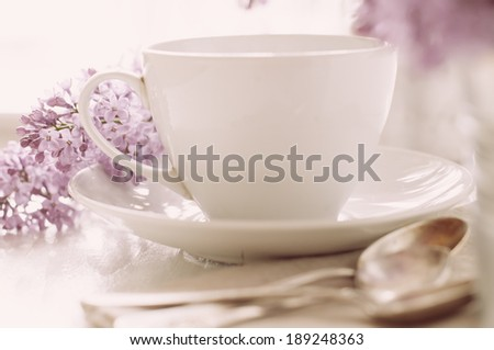 Delicate morning tea table setting with lilac flowers, vintage spoons and utensils on a white wooden board - stock photo