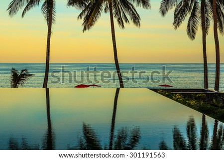 Delicate sunset on the popular resort island of Koh Samui. Palm trees reflected in smooth water of the pool on the beach - stock photo