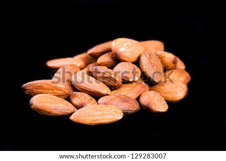 Delicious almonds isolated on black - stock photo