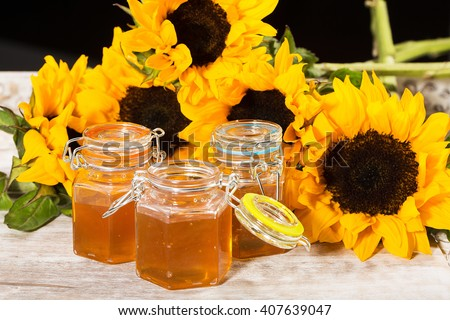 Delicious and fresh honey with colorful sunflowers - stock photo