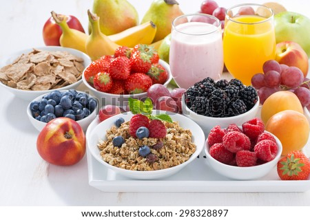 Delicious and healthy breakfast with fruits, berries and cereal on wooden tray, close-up - stock photo