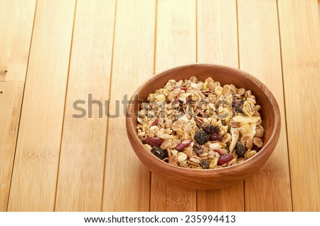 Delicious and healthy cereal in bowl with milk and bananas on table in room - stock photo