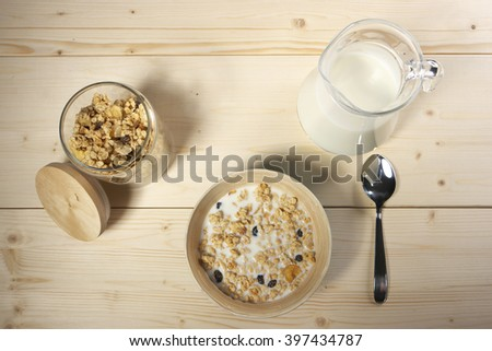 Delicious and healthy cereal in bowl with milk on table - stock photo