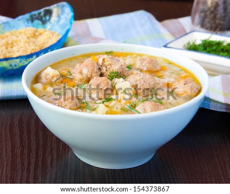 Delicious and healthy hot soup with barley bulgur and small meat balls, warming food - stock photo
