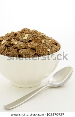 Delicious and nutritious bran flakes cereal, high in bran, high in fiber, served in a beautiful  French Cafe au Lait Bowl with wide rims.  This healthy bran cereal will be an aid to digestive health. - stock photo
