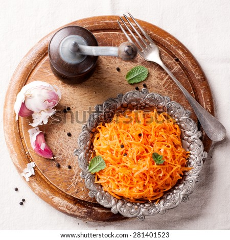Delicious and spicy carrot spaghetti with ginger, garlic, chili and olive oil on round chopping board. Top view.  - stock photo