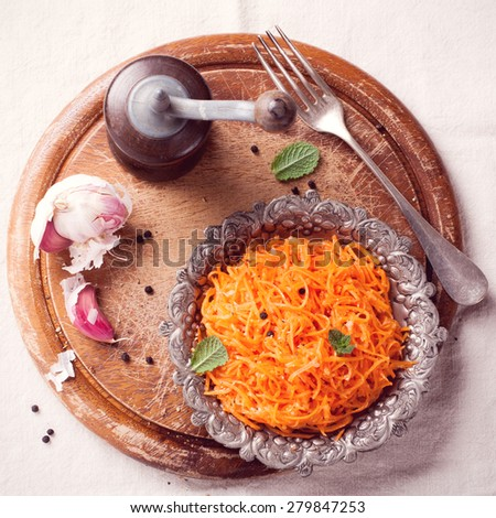 Delicious and spicy carrot spaghetti with ginger, garlic, chilli and olive oil on round chopping board. Top view. Toned - stock photo