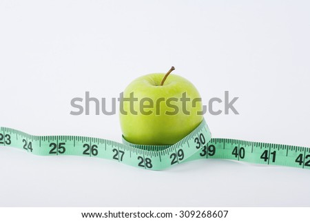 Delicious and tasty green apple with green measuring tape - diet, fitness, lifestyle, healthy and vegetarian concept - stock photo