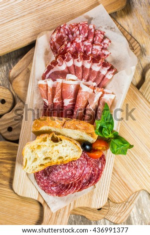 Delicious and tasty meat dishes. Ham, salami, prosciutto. Italian appetizers. - stock photo