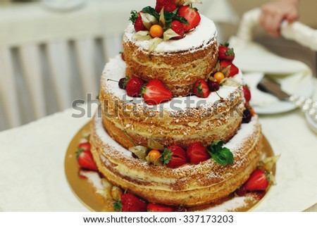 Delicious and tasty wedding cake with coconut strawberries and cream layered close-up - stock photo