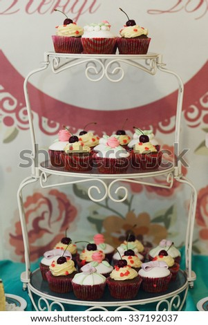 Delicious and tasty wedding dessert table with cupcakes and pies and macaroons wti frosting and cherries - stock photo