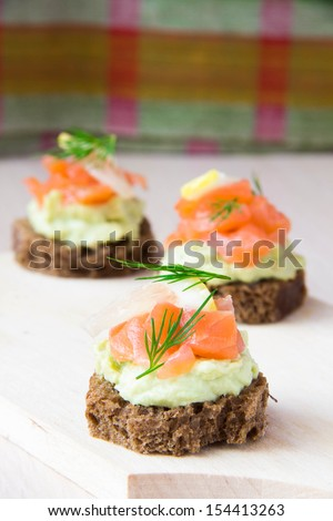 Delicious appetizer canapes of black bread, avocado and red fish salmon on board - stock photo