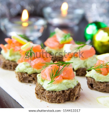 Delicious appetizer canapes of black bread, avocado and red fish salmon on board for New Year's celebratory table - stock photo