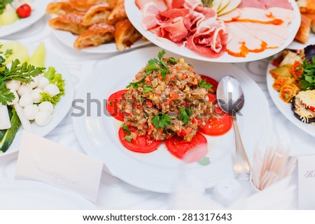 Delicious appetizer close-up. Eggplant salad with tomato and feta cheese, decorated with greens, vegetarian food - stock photo