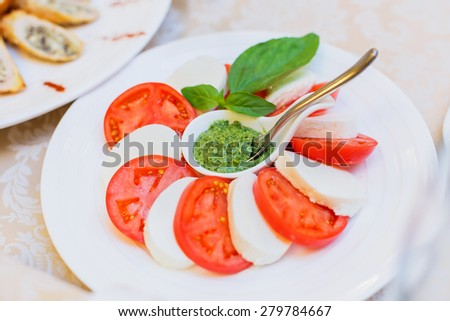 Delicious appetizer close-up. Fresh tomatoes and cheese with spicy hot sauce. Holiday banquet menu - stock photo
