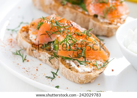 delicious appetizer with bread, salted salmon and cream cheese, close-up, top view - stock photo