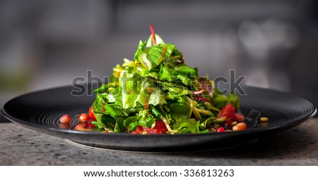 Delicious appetizer with herbs and pomegranate seeds on black plate close up - stock photo