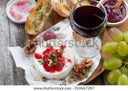 delicious appetizers for wine - camembert, berry jam, toast and fresh grapes, top view - stock photo