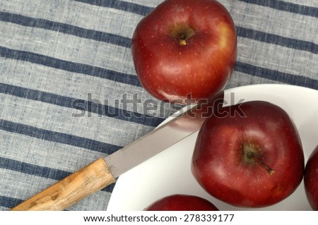 Delicious apples in white plate with knife on striped tablecloth. - stock photo
