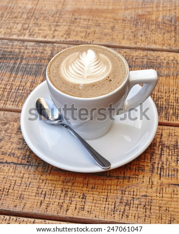 delicious art cappuccino coffe cup on wooden background - stock photo
