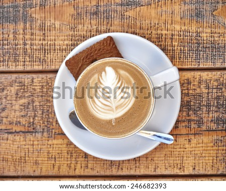 delicious art capuccino coffee cup on wooden background, space for typing - stock photo