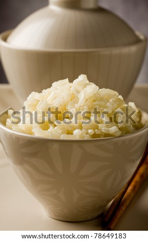 delicious asian rice plate with chopsticks on glass table - stock photo