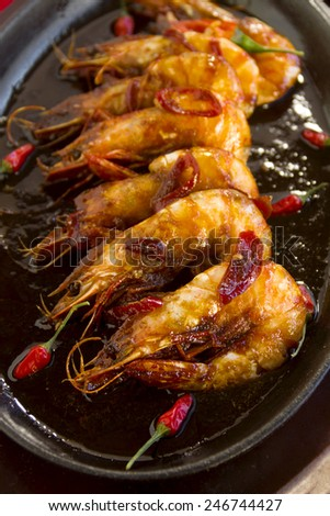 Delicious Asian sizzling chilli shrimps served in a hot cast iron platter. - stock photo